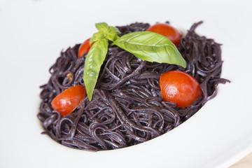 Pasta al nero di seppia su piatto bianco