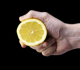 Man's hand squeezing half of lemon