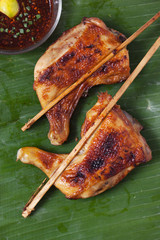 thai grilled chicken with spicy sauce on banana leaf