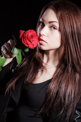 Closeup portrait of a pale beautiful young woman with a red rose