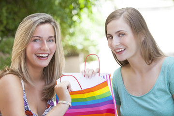 Happy young women with shopping bags smiling outdoors