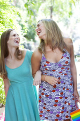 Happy young blonde friends with shopping bags