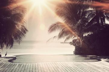 Bright sunburst over a luxury infinity pool