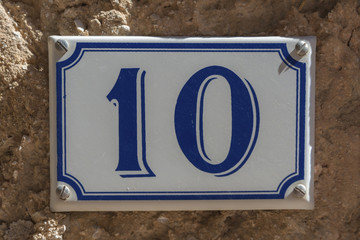 Blue and white number 10 ceramic plaque on a house