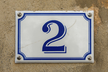 Blue and white number 2 ceramic plaque on a house