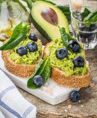 Avocado sandwich and blueberry on the wooden background