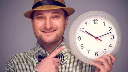 Young hipster man pointing on clock on dark grey background