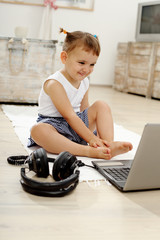 Young girl smiling with laptop in the living room