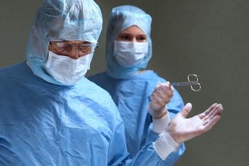 Assistenzärztin reicht Chefarzt OP Schere