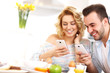 Happy couple eating breakfast and using smart phone