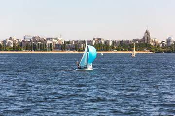Sailing vessels on the river against city