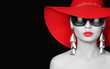 Woman in red hat and sunglasses over black background