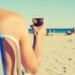 young man hanging out on the beach with a cola drink, filtered