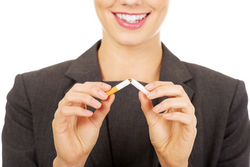Businesswoman breaking a cigarette.
