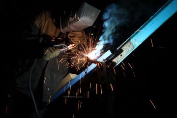 Welding operator welds metal constructions
