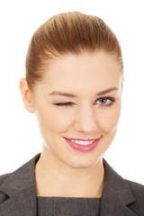 Businesswoman blinks her eye.