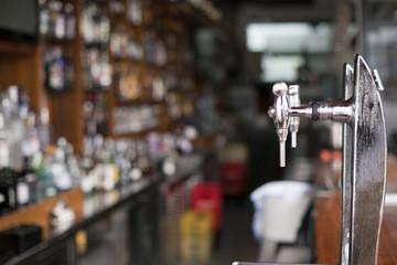 Grifos de cerveza con barra de licores al fondo