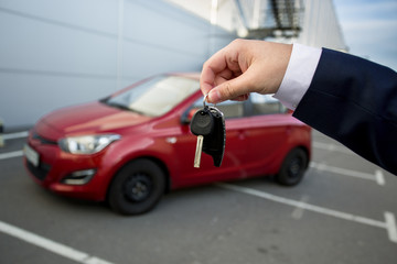 Car salesman showing keys with alarm remote
