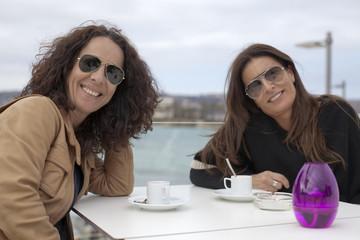 Amigas tomando un café en terraza junto al mar