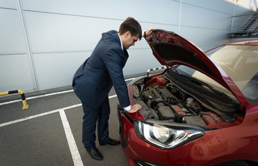 Stressed businessman looking under the car hood