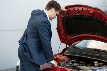 car sales manager looking under the bonnet of automobile