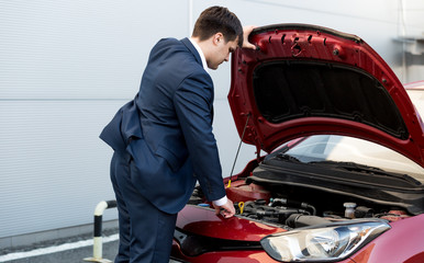 businessman in suit opening bonnet of open car