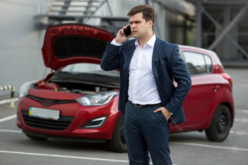 Portrait of man standing at broken car and calling repair servic