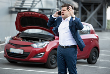 angry man talking by phone because of broke down car