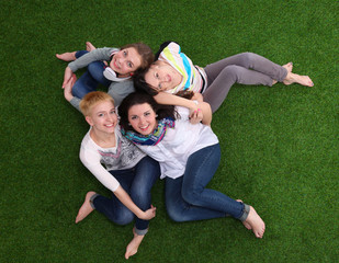 Four young women sitting  on green grass