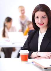 Attractive businesswoman sitting  on desk in the office with cup