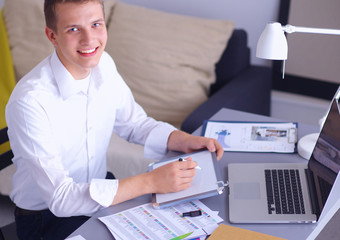Young businessman working in office, standing near desk