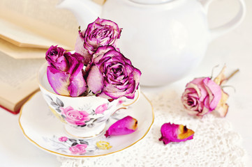 Vintage tea setting with dry roses on white background