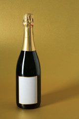 champagne bottle with blank label on gold