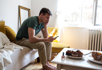 Man sitting on couch and using phone at home in the living room