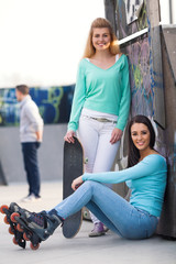 Two teenage skater girls hanging out in a skateboard park
