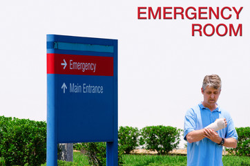 Man with a wrist injury walking by Emergency Room sign