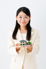 asian businesswoman with miniature house