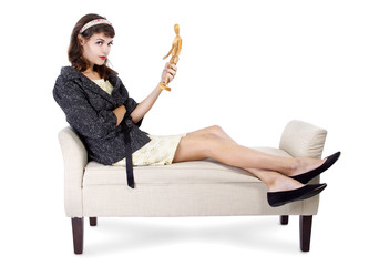 female holding a wooden figurine imagining the perfect man