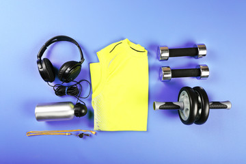 Sports equipment and T-shirt on color table, top view