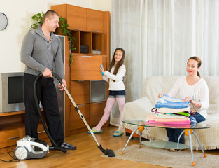 Mother, father and girl doing general cleaning