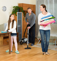 Family of three tidying up a room