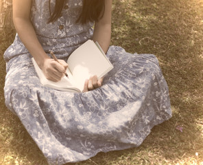 a young girl writing into her diary