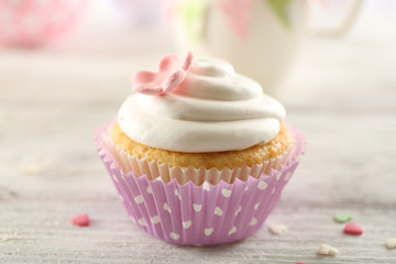Delicious cupcake on table on light background