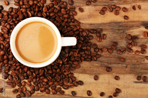 Cup of coffee with grains on rustic wooden table, top view