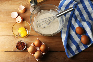Preparation cream with eggs in glass bowl on wooden background