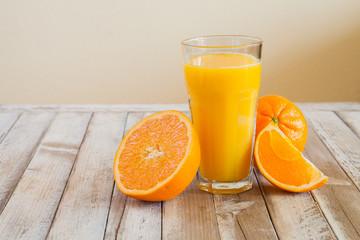 Orange fruit and glass of juice on white wooden background