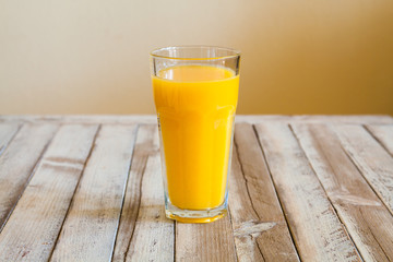 Glass of orange juice on white wooden background