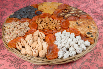 Assorted nuts and dried fruits in wicker plate