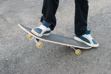 Skateboarder rides on the pavement.