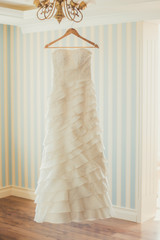 White Wedding dress hanging on a shoulders.